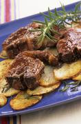 Lamb chops with rosemary and sliced potatoes - stock photo