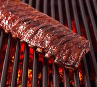 Whole Rack of Pork Ribs on Grill with Barbecue Sauce - stock photo