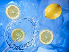 Stream of water running onto lemons and lemon slices - stock photo