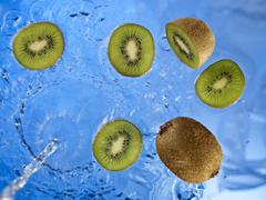 Stream of water running onto kiwi fruit and kiwi fruit slices Stock Photos