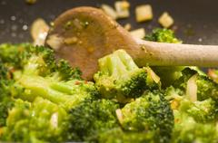 Stirring broccoli in a frying pan with a wooden spoon - stock photo