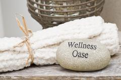 Stone with the words 'Wellness Oase' (Oasis of Wellness) and towels Stock Photos
