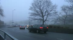 Cars at roundabout in fog with stark winter trees Stock Footage