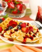 Waffles Topped with Strawberries, Blueberries and Fruit Sauce - stock photo