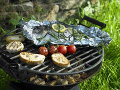 Foil-wrapped bream on a barbeque Stock Photos