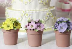 Wedding cake and artificial pansies - stock photo