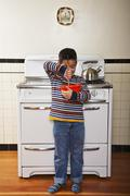 Six Year Old Boy Stirring Bowl In Front of a Stove in the Kitchen Stock Photos