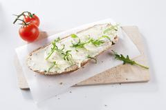 Bread and butter with rocket on a board - stock photo