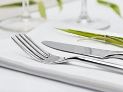 Knife and fork on fabric napkin Stock Photos