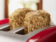 Slices of wholemeal toast in toaster Stock Photos