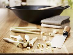 Lemon grass with cleaver in front of wok - stock photo