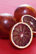 Blood oranges, whole and halved - stock photo