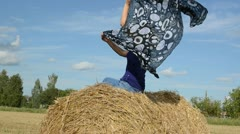 Blond woman sit straw bale field hold headscarf scarf move wind Stock Footage