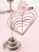 Wire heart with pink flower on stand - stock photo