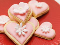 Pink heart-shaped biscuits with sugar flowers - stock photo