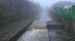 River flowing rapidly through town, man walks his dog on tow path in fog Stock Footage