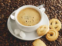 A cup of coffee with sugar cubes and biscuits Stock Photos