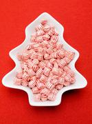 Red and white striped peppermints in dish - stock photo