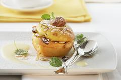 Baked apple with almonds and raisins Stock Photos