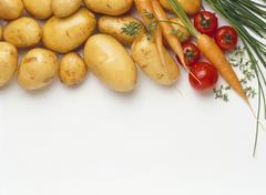 Potatoes, carrots, tomatoes and chives - stock photo