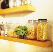 Pasta in storage jars, basil - stock photo