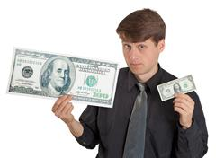 young man holding large and small money - stock photo