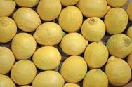 Stock Photo of fresh yellow lemon heap in container, food