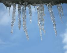 icicles heap on blue sky, winter environment - stock photo