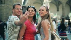 Three friends of tourist taking photo in the old town, steadycam shot - stock footage