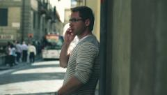 Young man talking on cellphone in the city, steadycam shot - stock footage