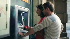 Young couple withdrawing money from an ATM, steadycam shot - stock footage
