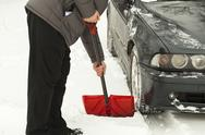 Man with shovel clears snow  around the car Stock Photos