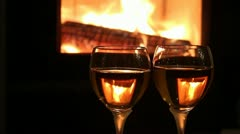 Wine glases in front of fireplace fire Stock Footage