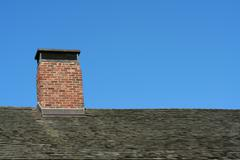 old roof and chimney with blue sky - stock photo