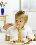 Boy eating spaghetti with tomato sauce - stock photo