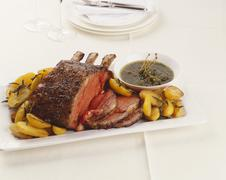 Fore rib of beef with roast potatoes and caper sauce - stock photo