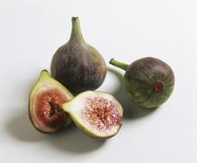 Whole and halved fresh figs - stock photo