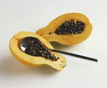 Removing papaya seeds with a spoon Stock Photos