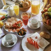 Breakfast table with juices, cold cuts and fruit Stock Photos