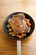 Beefsteak with vegetables in frying pan Stock Photos