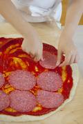 Girl putting slices of salami on pizza Stock Photos