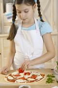 Girl putting tomatoes on pizza - stock photo