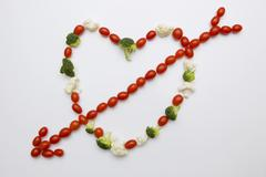 Tomatoes, broccoli and cauliflower forming heart with arrow - stock photo