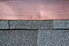 Stock Photo of black asphalt roofing shingles with copper flashing