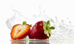 Strawberries with splashing water - stock photo