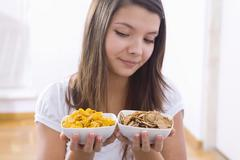 Girl holding two bowls of cornflakes - stock photo