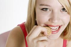 Young woman biting into a mini sandwich biscuit Stock Photos