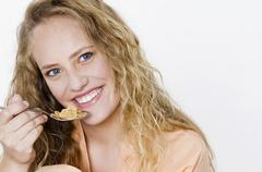 Young woman eating a spoonful of cornflakes Stock Photos