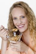 Young woman holding a glass with cornflakes Stock Photos