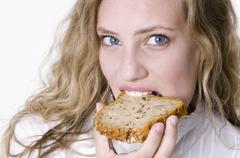 Young woman bitung into a slice of grannary bread Stock Photos